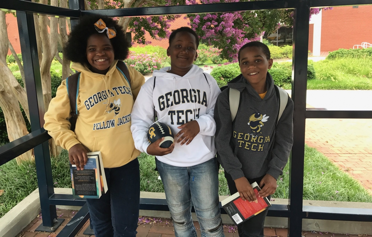 School and Community Engagement - three students pose in Georgia Tech sweatshirts